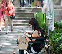 A park visitor uses her tablet computer in Bryant Park in New York on Tuesday, August 21, 2012 (© Richard B. Levine)