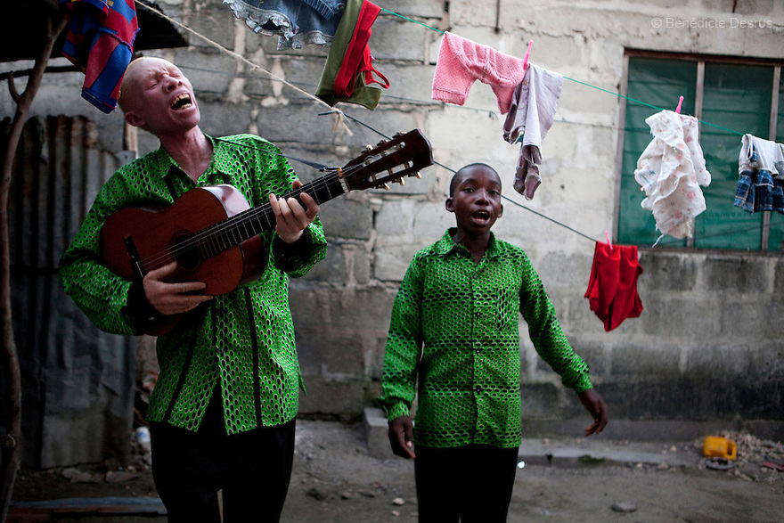 June 26, 2010 - Dar Es Salaam, Tanzania - Augostino Msisi, a 49 year old Tanzanian albino and his 15 year old son Kaloli practice music in the backyard of their house for their band Agustino Family singers. Albinism is a recessive gene but when two carriers of the gene have a child it has a one in four chance of getting albinism. Tanzania is believed to have Africa' s largest population of albinos, a genetic condition caused by a lack of melanin in the skin, eyes and hair and has an incidence seven times higher than elsewhere in the world. Over the last three years people with albinism have been threatened by an alarming increase in the criminal trade of Albino body parts. At least 53 albinos have been killed since 2007, some as young as six months old. Many more have been attacked with machetes and their limbs stolen while they are still alive. Witch doctors tell their clients that the body parts will bring them luck in love, life and business. The belief that albino body parts have magical powers has driven thousands of Africa's albinos into hiding, fearful of losing their lives and limbs to unscrupulous dealers who can make up to US$75,000 selling a complete dismembered set. The killings have now spread to neighboring countries, like Kenya, Uganda and Burundi and an international market for albino body parts has been rumored to reach as far as West Africa. Photo credit: Benedicte Desrus