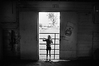 A young girl looks out of a stable door at the fairgrounds in Great Falls, Montana, USA.