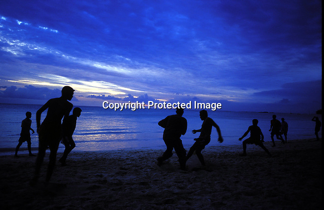 dicomau00022.Foreign Country.  Mauritius.Youths playing soccer on the beach as the sunssets on July 4, 2003, on Mauritius. The island, located in the Indian Ocean, is a popular place for tourists. .©Per-Anders Pettersson/ iAfrika Photos