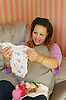Pregnant young woman sitting on sofa looking at baby clothes smiling,