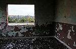 A look through the window of an abandoned school toward Dunavtsi, a town of waning population in Bulgaria, on October 27th, 2014. Bulgaria has the most extreme population decline in the world &mdash; much of it due to post-1989 emigration, high death rates and low birth rates. There are so few people of child-bearing age in the nation that population statistics project a 30-percent decrease by 2060, from 7.2 million to just over 5 million. In other words,&nbsp;Bulgaria&rsquo;s population declines by 164 people a day, or 60,000 people a year &mdash; 60 percent of them aged over 65.<br /> <br /> This photo is from a project that aims to gauge the state and effect of democracy in the former Soviet satellite nation Bulgaria, two and a half decades after the fall of the Berlin Wall. The story of democracy in Bulgaria at age 25 is a cautionary tale about transplanting one-size-fits-all Western values to a nation still undergoing social and economic upheaval. Bulgaria is still one of the poorest, most corrupt nations in the European Union, its post-1989 hopes wilted by political instability, high crime rates and skyrocketing inflation. While Bulgarians can now freely vote and protest without much threat to their freedom, their new oppressor is corruption - which is at a 15 year high, across political and civil sectors alike. The ennui is so casually etched on the passerby's face that it becomes routine - one that fits in sadly well against a startling backdrop of rotting architecture, joblessness, and a vast population decline. Despite what democracy has changed in Bulgaria, the daily struggles of its populace remain largely untouched, trapped in a post-communist time capsule.