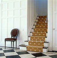In the entrance hall the painted white panelling and black and white marble floor are beautifully complementd by a yellow star-patterned stair carpet