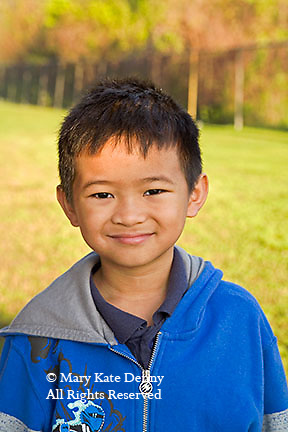 Vietnamese American second grade male smiles looking at camera in headshot outdoors in school yard