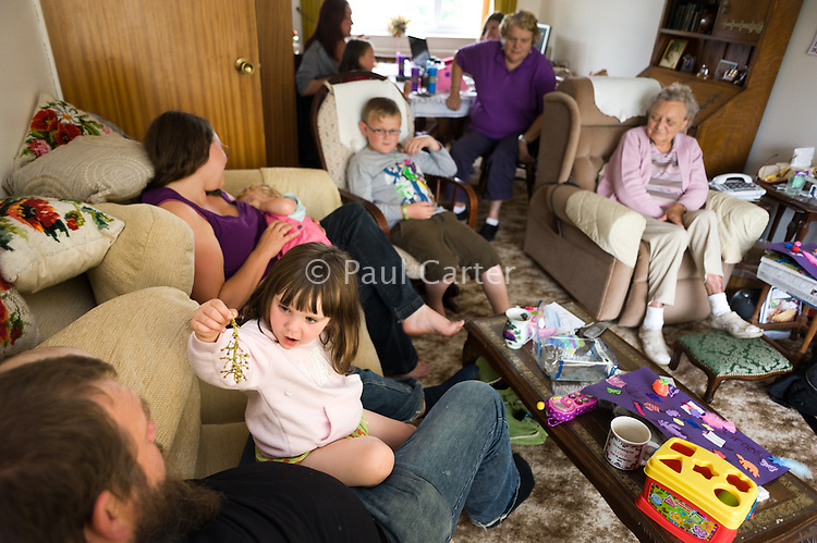 A mother breastfeeding her toddler in the living room at a family gathering.<br /> <br /> 23 August 2011<br /> Hampshire, England, UK