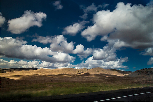White puffy clouds hover over the farmland along Highway 46 in Central California