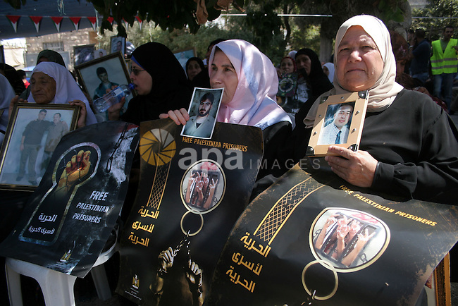 Palestinians hold pictures of relatives as they protest to demand the release of Palestinian prisoners from Israeli jails on September 26, 2010 in the West Bank city of Hebron. Photo by Mamoun Wazwaz