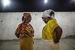 RIO DE JANEIRO, BRAZIL - JANUARY 24: Two women talk outside the case, or candomble temple, during a ceremony, in Rio de Janeiro, Brazil, on Saturday, Jan. 23, 2015. Brazil's Afro-Brazilian religions which in recent years have come under increasing threats and prejudice, particularly from the growing number of evangelical churches. Candombl&eacute; originated in Salvador, Bahia at the beginning of the 19th century when enslaved Africans brought their beliefs with them. Umbanda and candombl&eacute; are Afro-Brazilian religions practiced in mostly Brazil. <br /> (Lianne Milton for the Washington Post)