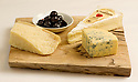 Three cheeses on a cutting board with cherry preserves