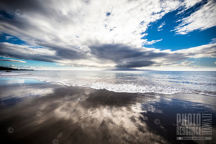 The Pacific Ocean reflects moving clouds over a beach in Ka'anapali, Maui; Lana'i can be seen in the distant center.