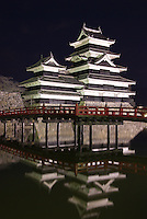 Matsumoto Castle, lit up at night, reflects in the still waters of its moat.