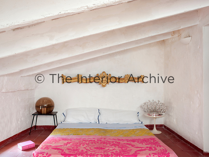 A simple, small attic bedroom has been given a theatrical twist with eclectic pieces and brightly coloured throws covering the mattress on the floor