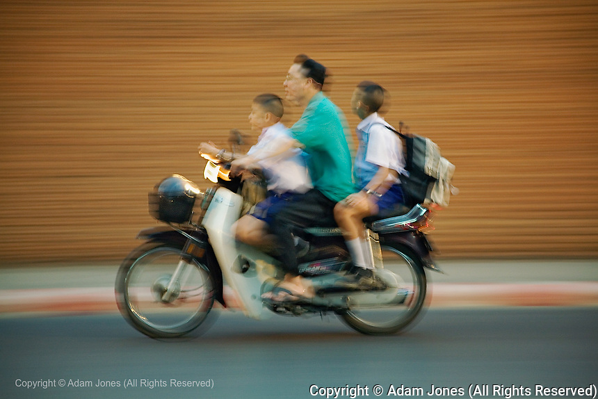 Three members of Thai family in motion on small motorcycle, Chiang Mai, Thailand