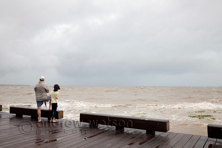 Locals watching a storm surge along the Cairns Esplanade.  Cairns, Queensland, Australia
