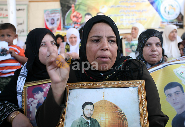 Palestinian women carry pictures of a jailed relative being held in an Israel prison, during a protest calling for their release at the International Red Cross building in Gaza City on October 26, 2009. There are some 11,000 Palestinians being held in Israeli jails currently. Photo by Mohammed Othman
