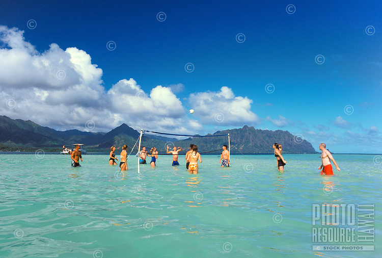 Vacationers enjoy playing volleyball during a high tide at the sand bars located in the middle of scenic Kaneohe Bay.