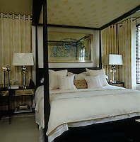 A large artwork of a Spanish fan hangs above the four-poster bed in the comfortable bedroom