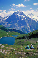 Two hikers admire the Swiss Alps, Switzerland. alpine landscape, mountains, geography, hiking, lake in a valley. Switzerland.