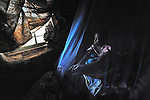 A girl looks outside from her bed, covered with an anti-malarial mosquito net, in Dundube Kadambo, Malawi.