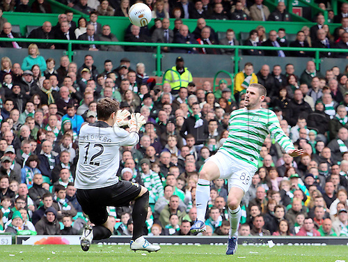 21.04.2013 Glasgow, Scotland. Gary Hooper chips the ball over Antonio Reguero  during the Scottish Premier League game between Celtic and Inverness Caledonian Thistle from Celtic Park.