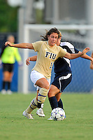 27 August 2011:  FIU's Kelly Ann Hutchinson (12) gets the ball past Akron's Ashley Hughes (7) in the first half as the FIU Golden Panthers defeated the University of Arkon Zips, 1-0, at University Park Stadium in Miami, Florida.