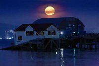 A full moon, known as Harvest Moon is seen rising over the RNLI boathouse in Mumbles Pier, near Swansea, Wales, UK. Tuesday 25 September 2018