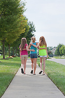 Three Young Girls Walking together, Arm in Arm, in a Residential Neighborhood.  Selective focus on the Kids.
