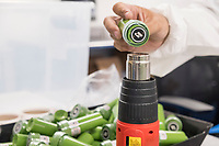 """A worker applies safety seals to dram bottles containing high-dose """"g-cap"""" gel capsules at the production and packaging facility for Garden Remedies, a medical cannabis producer, in Fitchburg, Massachusetts, USA, on Fri., Feb. 22, 2019. The bottles have a variety of safety labels, including stickers that read """"Not safe for children"""" and """"Contains THC"""" in addition to other safety features."""