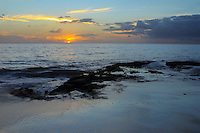 Sunset reflects off of the ocean and water-saturated sand at Makua Beach, Waianae, O'ahu.