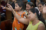 People raise their hands in blessing during worship at Knox United Methodist Church in Manila, Philippines. The service is part of a weekday program where the church opens up to poor people in the neighborhood, offering showers, food, fellowship, and an opportunity to worship together.