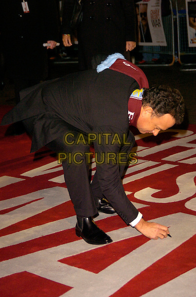 TOM HANKS.Charlie Wilson's War - UK film premiere, Empire Leicester Square, London, England..January 9th, 2008.full length bending leaning over gesture black suit maroon burgundy aston villa football club scarf marker pen picking up profile signing autograph .CAP/CAN.©Can Nguyen/Capital Pictures