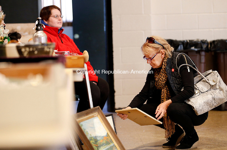 Torrington, CT- 11 April 2015-041115CM05-  Margot Gordon of Torrington looks at an item during a tag sale at the Coe Memorial Park Civic Center in Torrington on Saturday.  The event will help benefit the city's fireworks fund.  The Sullivan Senior Center also held an Antique's Appraisal and tag sale on Saturday.   Christopher Massa Republican-American