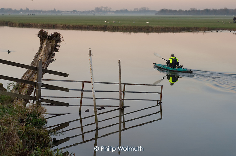 A man paddles a canoe on the River Thames in Port Meadow, Oxford, at dusk