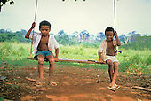 Juruena, Amazon, Brazil. Two young boys sitting on a home made swing.