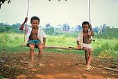 Juruena, Amazon, Brazil. Two young boys sitting on a home made swing.