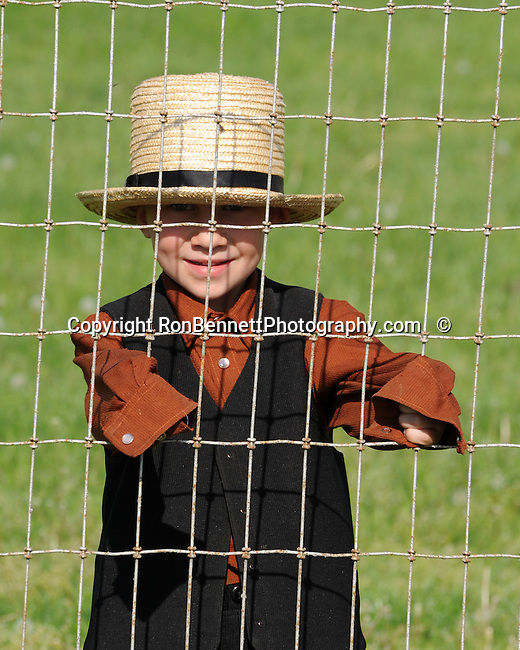 "Amish boy behind fence Pennsylvania Dutch country in Lancaster County PA, Pennsylvania Dutch in Amish Country Lancaster County Pennsylvania, Amish, Horse and buggy with amish family on backroads of Pennsylvainia, buggy, amish family, buggy and horse, Commonwealth of Pennsylvania, Commonwealth of Pennsylvania, natives, Northeasterners, Middle Atlantic region, Philadelphia, Keystone State, 1802, Thirteen Colonies, Declaration of Independence, State of Independence, Liberty, Conestoga wagons, Quaker Province, Founding Fathers, 1774, Constitution written, Photography history, Fine art by Ron Bennett Photography.com, Stock Photography, Fine art Photography and Stock Photography by Ronald T. Bennett Photography ©, All rights reserved copyright Ron Bennett Photography.Com, FINE ART and STOCK PHOTOGRAPHY FOR SALE, CLICK ON  ""ADD TO CART"" FOR PRICING,"