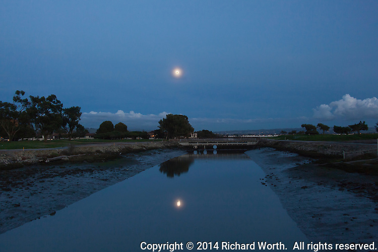 A day and half away from being the Full Cold Moon, the almost full moon rises over the Tony Lema Golf Course along San Francisco Bay, its light reflected in the flood control channel waters.