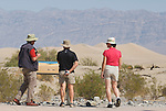 Park visitors stop to read an interpretive sign at Mesquite Flat sand dunes, which features a photo of a sidewinder by wildlife photographer Dan Suzio. Death Valley National Park, California
