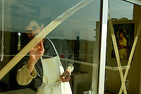 Baghdad, Iraq, March 12, 2003.An employee cross-taping hotel windows in prevention of a potential US air strike against Baghdad.