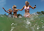 Laurie Boyle of Green Bay, left, Tina Rafowitz of Minneapolis, Minn., and Taylor Boyle of Green Bay work their way into the water at Whitefish Dunes State Park in Door County on July 29, 2005.