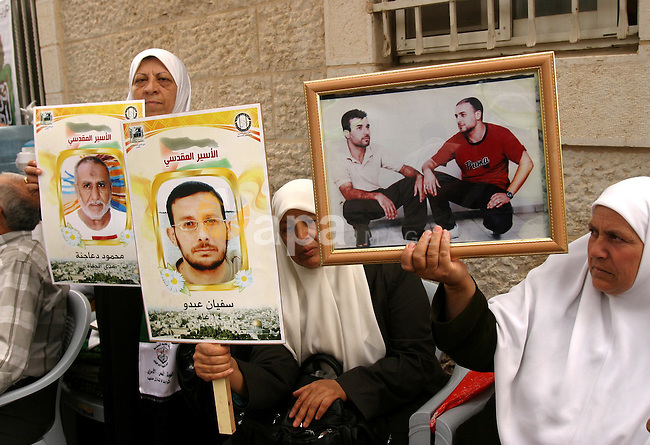 Palestinian protesters hold up banners and portraits of a prisoners jailed in Israel, during a Sit-in held in the neighborhood of Sheikh Jarrah, in front of the Red Cross in the West Bank city of Jerusalem, April 30, 2012. Over the past week, over 1,350 Palestinian prisoners have begun an open-ended hunger strike to protest against the conditions in which they are being held in Israeli jails. Photo by Mahfouz Abu Turk