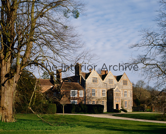 The facade of Hambledon manor house features a flint and brick effect traditional to the south of England