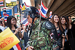 Apr. 19 2010 - BANGKOK, THAILAND: Thai soldiers move among civilians on the street in the Silom financial district of Bangkok Monday. Hundreds of Thai soldiers, including reservists and front line units, and riot police moved into the Silom financial district Monday, not far from the red-shirts' main protest rally site, in Ratchaprasong. The heavy show of force is to prevent the Red Shirts from entering the Silom area. Many of soldiers were greeted as heros by workers in the area, who oppose the Red Shirts.   Photo by Jack Kurtz