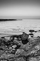 Stenar på en häll på Nåttarö vid havet i Stockholms skärgård i svartvitt. / Stones on a rock by the sea on Nåttarö in Stockholms archipelago Sweden.