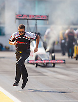 Mar 15, 2019; Gainesville, FL, USA; NHRA crew member Gary Pritchett runs ahead of top fuel driver Steve Torrence as he does a burnout during qualifying for the Gatornationals at Gainesville Raceway. Mandatory Credit: Mark J. Rebilas-USA TODAY Sports