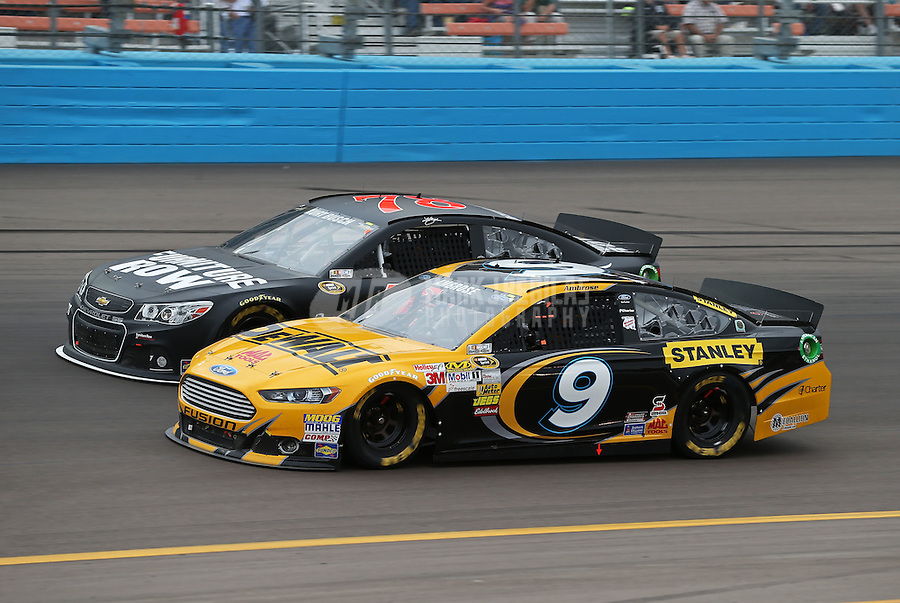 Mar. 3, 2013; Avondale, AZ, USA; NASCAR Sprint Cup Series driver Marcos Ambrose (9) races alongside Kurt Busch during the Subway Fresh Fit 500 at Phoenix International Raceway. Mandatory Credit: Mark J. Rebilas-