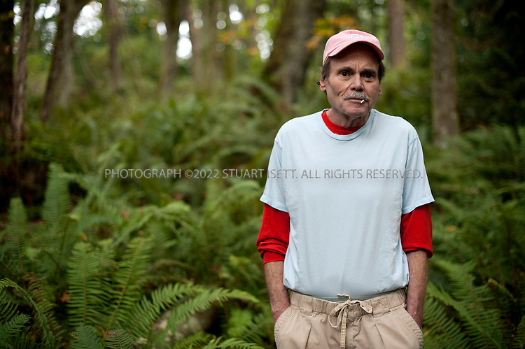 9/24/2009--Clinton, WA..Writer Pete Dexter, born 1943, posing in the woods near his home. Dexter was the recipient of the 1988 National Book Award for Fiction for his novel Paris Trout. ..©2009 Stuart Isett. All rights reserved.