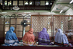 KADEEJEEN, BANGKOK, THAILAND, DECEMBER 2012:.Friday Prayer in one of the mosquee in Kadeejeen, here muslim, christians and buddisth coexist in peacedul Armony, Dec 2012...The Kadeejeen neighbourhood comprises six communities  Wat Kalaya, Kudeejeen, Wat Prayurawong, Wat Bupparaam, Kudee Khao and Roang Kraam...Ever since the Thonburi era (in the 17th Century), these historic neighbourhoods have maintained the diverse cultural heritage of three religions and four beliefs (Theravada Buddhism, Mahayana Buddhism, Christianity and Muslim) while coexisting in peaceful harmony...The neighbourhood is still characterised by Bangkok's traditional urbanism which is that of a fine-grained, religious establishment-centred urban structure with close-knit social cohesion. ©Giulio Di Sturco/Reportage by Getty Images.