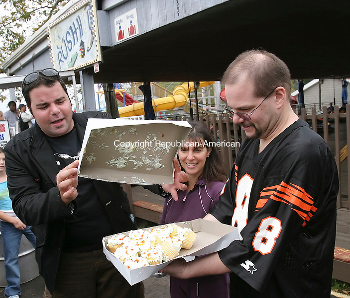 MIDDLEBURY; CT; 23 SEPTEMBER 2006; 092306BZ03- Food Network's &quot;Ham on the Street&quot; host George Duran, left, checks cupcakes held by Chris Buckley, of Woodbury, as Margie Iaiennaro (CQ), of Southbury, center, looks on during filming for a segment at Quassy Amusement Park in Middlebury Saturday afternoon.   Iaiennaro and Buckley carried cupcakes in different containers and crashed around in bumper cars to test the containers.<br />  Jamison C. Bazinet Republican-American