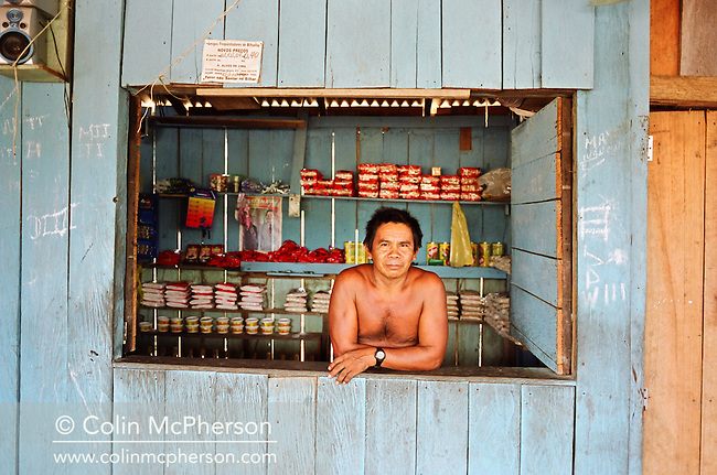 A barman standing at the hatch of his bar which doubles as a village shop in a small settlement by the Tapajos river. The Floresta Nacional do Tapajos (FLONA), a 6500 km2 protected reserve, was home to several small communities which lived on the banks of the Rio Tapajos. Most communities did not have electricity or running water and access to the villages was by unpaved dirt roads from Santarem and Highway BR163.